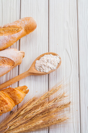 coposition of baguettes croissant ears wheat wooden spoon wit photo