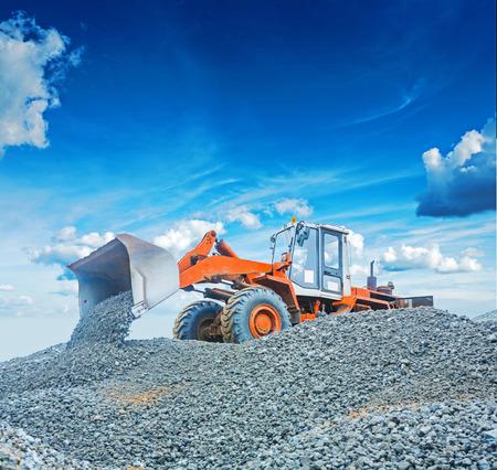 old wheel loader excavator working with  gravel