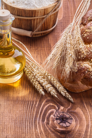 sweet bun: food and drink concept ears of wheat loaf sweet bun  bottle with oil bucket flour on vintage boards Stock Photo