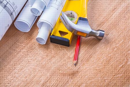 rolls of blueprints level hammer pencil construction concept photo