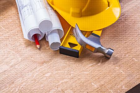 rolls of blueprints level hammer pencil yellow hardhat on wooden photo