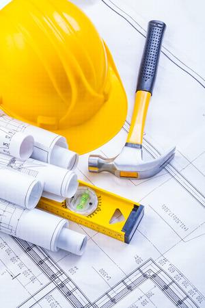 rolls of white blueprints helmet level claw hammer construction photo
