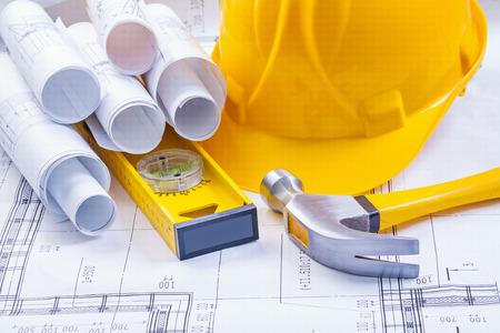 yellow hard hat: rolls of white blueprints helmet level claw hammer construction
