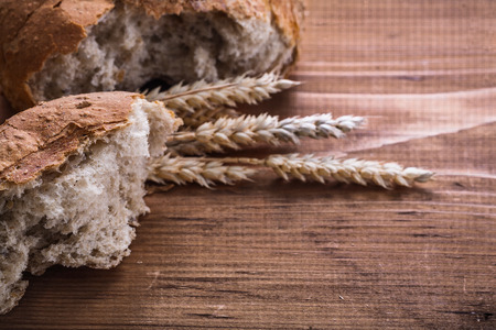 sliced bread: sliced bread and ears of rie on vintage wooden board concept Stock Photo