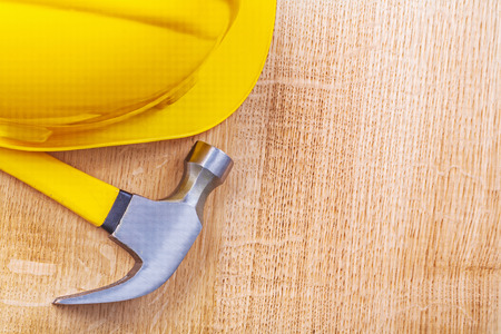 yellow hardhat and claw hammer on vintage wooden board copyspace photo
