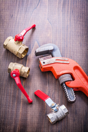 fixtures: plumbers fixtures and adjustable wrench on vintage wooden board Stock Photo