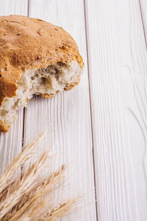 sliced bread: sliced bread and ears of wheat on white painted wooden boards wi