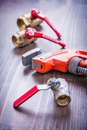 household fixture: adjustable wrench and plumbing fixtures on vintage wooden board