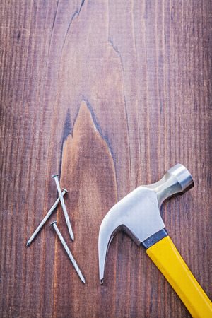 claw hammer nails on vintage wooden board with copyspace construction concept photo