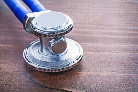 close up   head: close up head of medical stethoscope on vintage wooden board