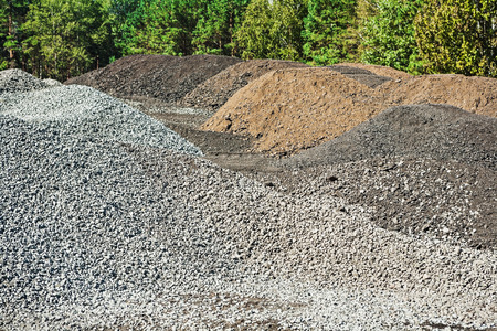 macadam: piles of gravel and mixed sand on construction site in forest
