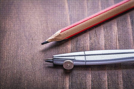 drafting tools: compass and pencil on vintage wooden board learning concept