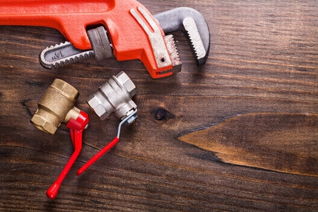 fixtures: monkey wrench and plumbers fixtures on vintage wooden board
