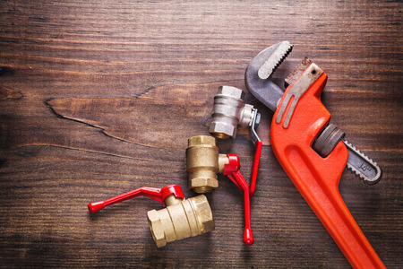 fixtures: organized copyspace two plumbers fixtures and monkey wrench on v