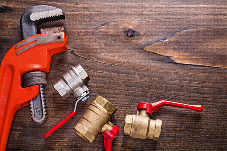 household fixture: organized copyspace plumbers fixtures and monkey wrench on vinta