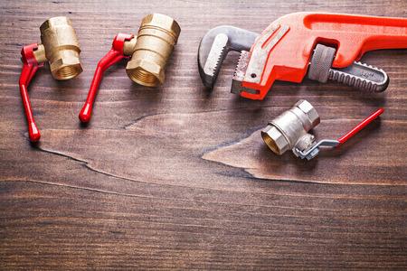 household fixture: organized copyspace plumbing fixtures monkey wrench on vintage w Stock Photo