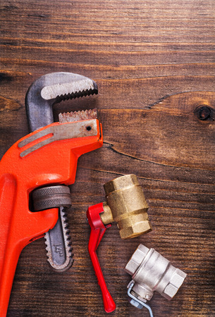 fixtures: plumbers fixtures and monkey wrench on vintage wooden board Stock Photo