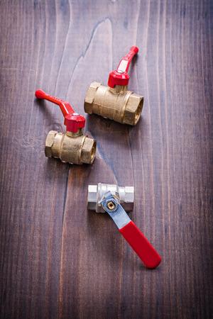 fixtures: three plumbers fixtures on vintage wooden board Stock Photo