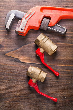 fixtures: two plumbers fixtures and monkey  wrench on vintage wooden board Stock Photo