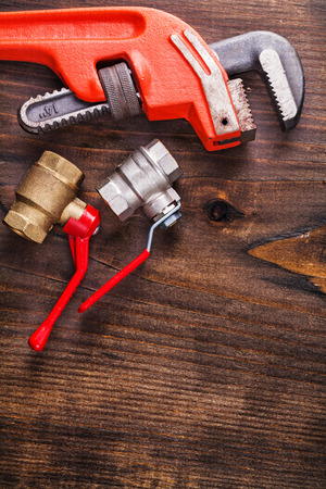 two plumbers fixtures and monkey wrench on vintage wooden board photo