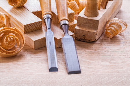 close up view on carpentry chisels wooden planks shavings plane