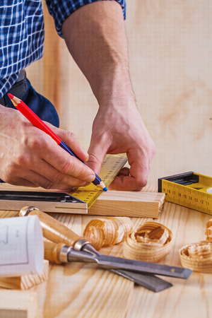 scobs: hands of carpenter drawing with pencil on wooden planks construc Stock Photo