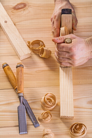 scobs: hands of carpenter with woodworkers plane construction concept