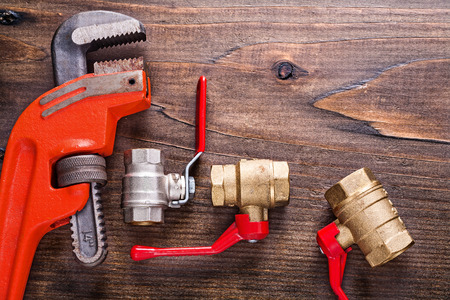 fixtures: plumbers fixtures with red handles and monkey wrench on vintage