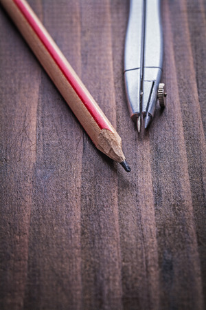 drafting tools: very close up view compass and pencil on vintage wooden board le