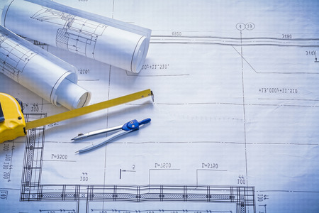 tapeline: two rolled blueprints tapeline compass with copyspace constructi Stock Photo