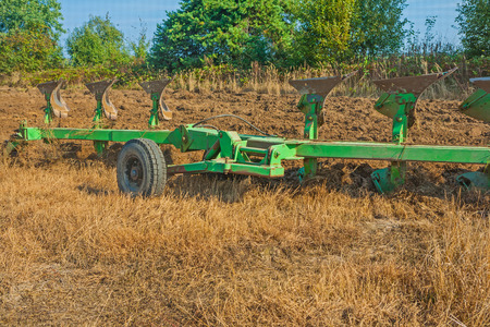 big set of plough on field in work agricultural concept photo