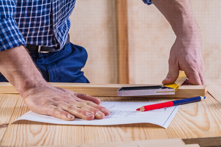 square ruler: hands of carpenter on table with blueprint square ruler and penc