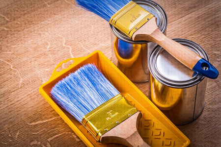 paint can: horizontal version paint can brushes tray on wooden board constr Stock Photo