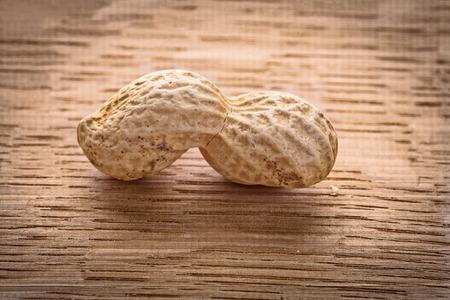 macroshot: macroshot single peanut on vintage wooden board food and drink c