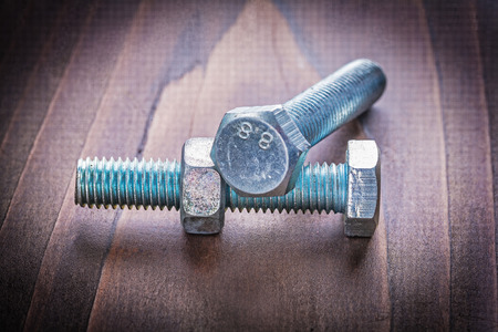 silver plated: two bolts and nut on vintage wooden board construction concept