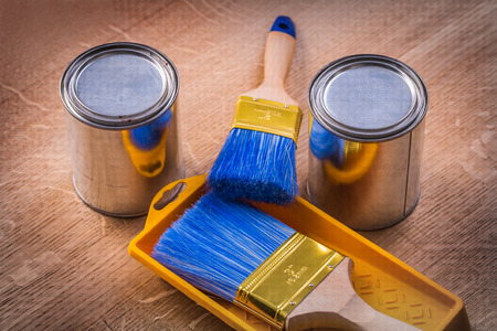 paint cans: two paint cans brushes tray on wooden board construction concept