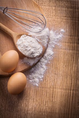 copysapce: aerial view two eggs flour spoon corolla on wooden board