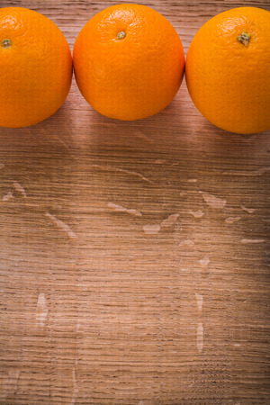 organized: three orange fruits on wooden table with organized copyspace