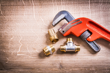 household fixture: Monkey Wrench And Brass Pipe Connectors On Wooden Board Stock Photo