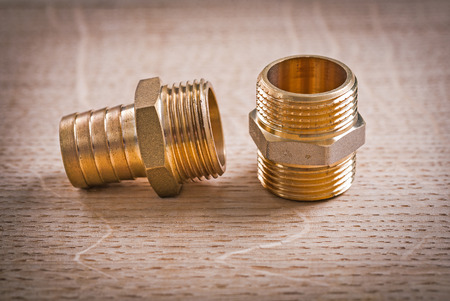 household fixture: Brass Pipe Connectors On Wooden Board Stock Photo