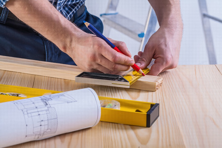 square ruler: carpenter sketching wooden plank close up view