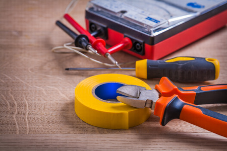 nippers: insulation tape, nippers, screwdriver and multimeter On Wooden Board Stock Photo