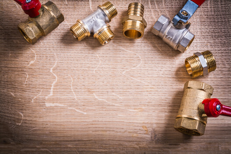 household fixture: Organized Copyspace Aerial View Brass Pipe Connectors On Wooden Stock Photo
