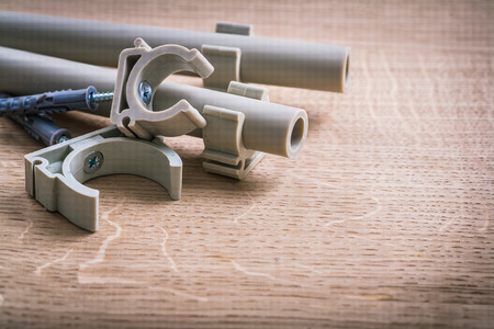 household fixture: Polypropylene Fixators And  Pipe  With Clips On Wooden Board Stock Photo