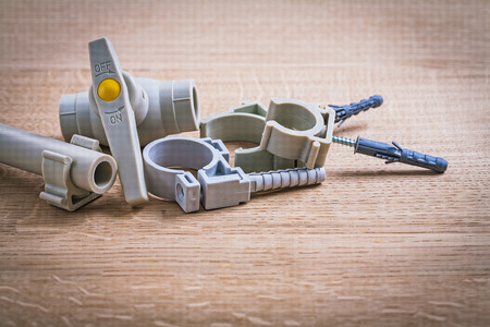 household fixture: Polypropylene Fixators And  Pipe  With Clips Water Valve On Wood