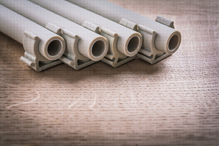 household fixture: Polypropylene Pipe With Clips On Wooden Board Stock Photo