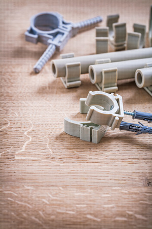 household fixture: Set Of Polypropylene Fixators And Pipe With Clips On Wooden Board