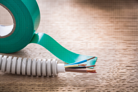 cordon tape: electric cable in corrugated pipe and roll of green insulating t