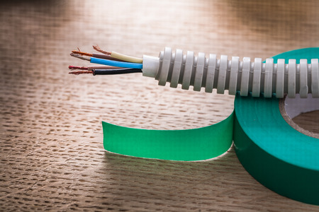 cordon tape: electric cable in corrugated pipe on roll of green insulating ta