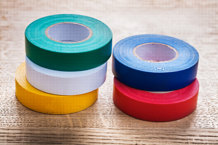 cordon tape: five colored rolls of insulating tape on wooden board constructi